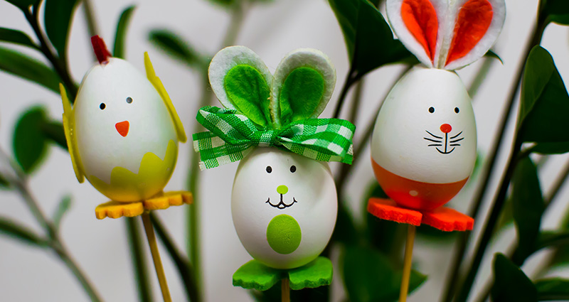 Easter decorations on sticks. Green plant in the background.