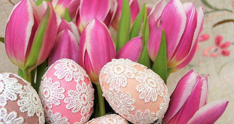Easter eggs decorated with lace. Pink tulips in the background.