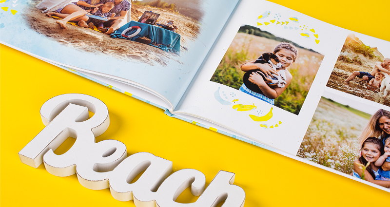 Family holiday photobook landscape placed diagonally with wooden letters creating the word BEACH below it.