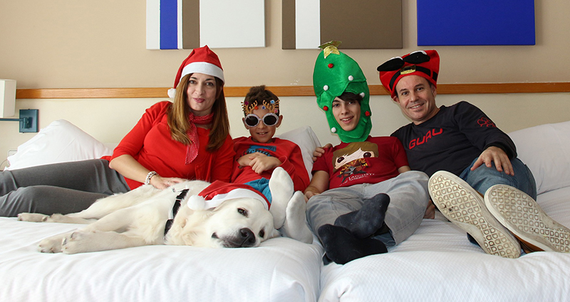 Family of four and a dog on the bed – each of them wearing a different Christmas hat or glasses.