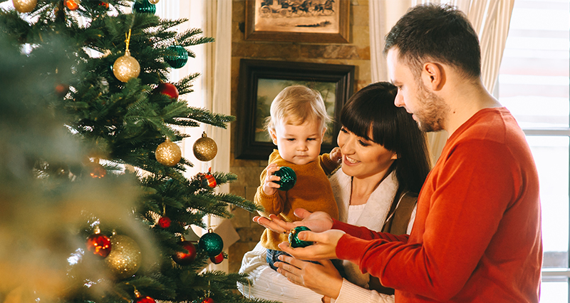Family of three decorating a Christmas tree