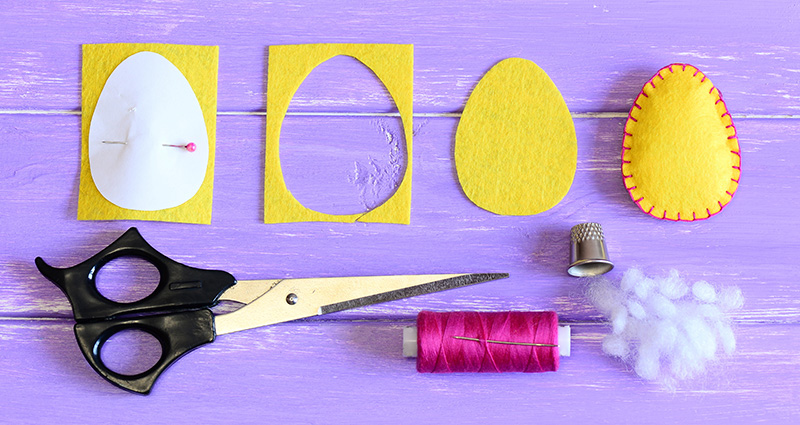 Felt eggs, scissors, thread, thimble and cotton on a purple table.
