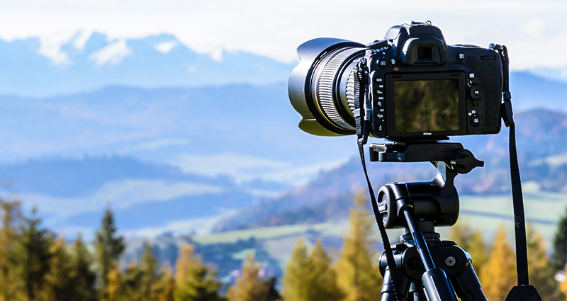 Focus on a camera mounted on a tripod, wood and mountains in the background