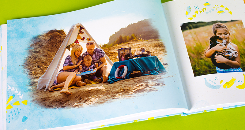 Focus on a framed photo of a family in a tent printed in a photobook, delicate cliparts on its pages