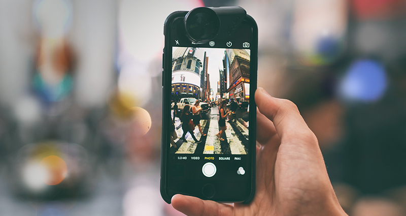 Focus on a hand holding a smartphone with a portable lens, people walking through the street on the screen; a blurred background