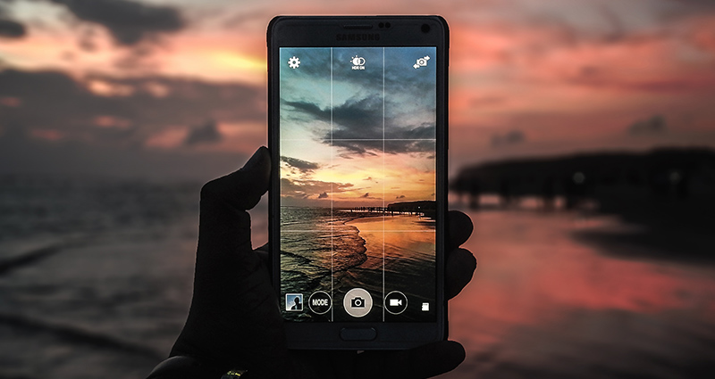 Focus on a hand holding a smartphone; a sunset on the screen.