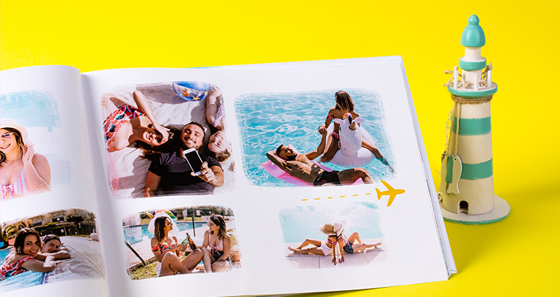Focus on a page of a holiday photobook with pictures of friends lying next to a ceramic figurine presenting a lighthouse