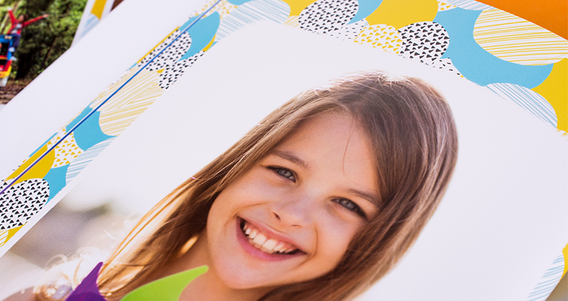 Focus on a photo showing a smiling girl who is holding a colourful fan. A photobook printed in 7C technology.
