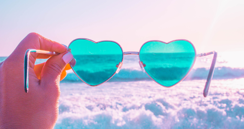 Focus on a woman's hand holding heart shaped sunglasses, sea waves in the background. There is a pink filter which has been added to the photo.