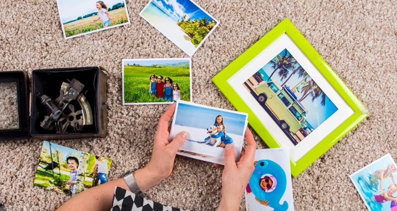 Focus on the hands of a person looking at summer photo prints lying on the carpet