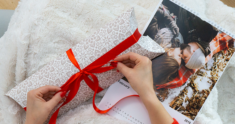 Focus on woman's hands who is resting under a blanket and wrapping a calendar box; a photo calendar next to it.