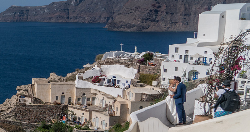 A photo of a photographer taking a photo of the newlyweds kissing on one of the terraces in Santorini. The sea in the background.