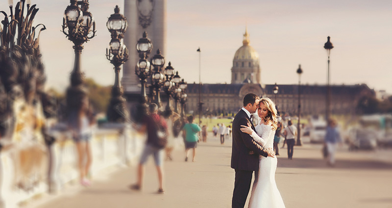 A photo of a newlywed couple holding each other on one of the squares in Paris.