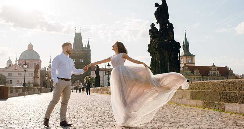 A photo of a newlywed couple dancing on a Charles Bridge in Prague.