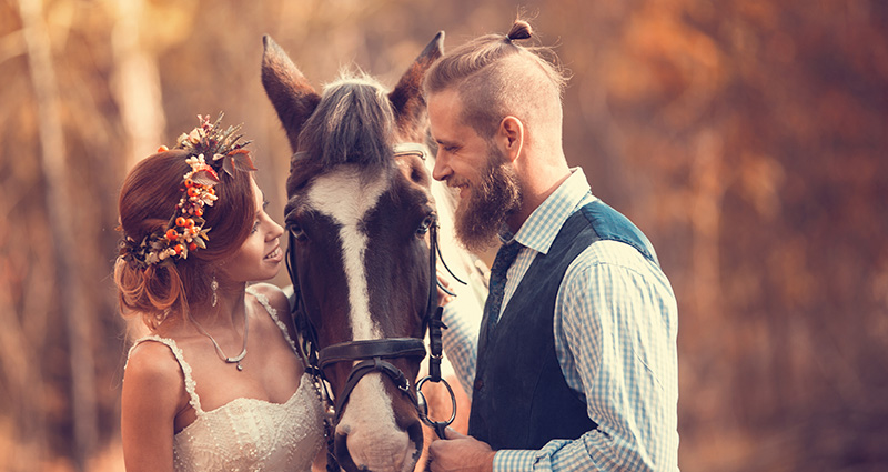A photo of a newlywed couple with a horse. Forest in the background.