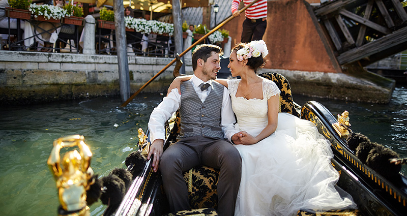 A photo of a couple on  a gondola in Venice.