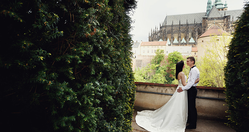 A photo of newlyweds in Prague. The castle in the background.