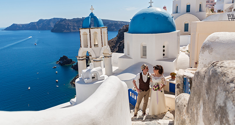A photo of newlyweds on Santorini. Churches with characteristic blue roofs in the background.