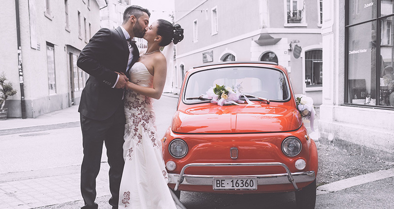 A photo of a newlywed couple kissing in an Italian alley. An old, red fiat near them.