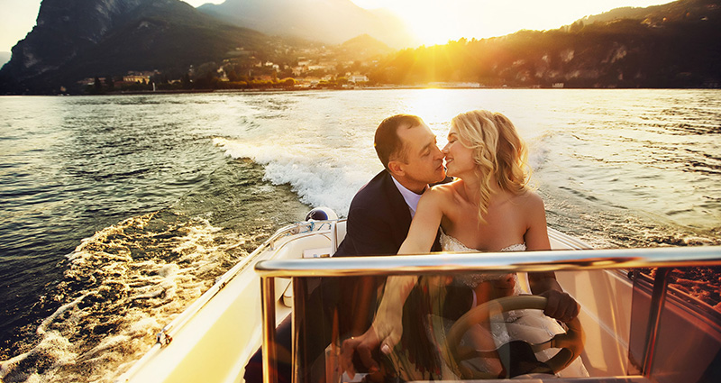 A photo of kissing newlyweds on a motorboat going across the Lake Como.