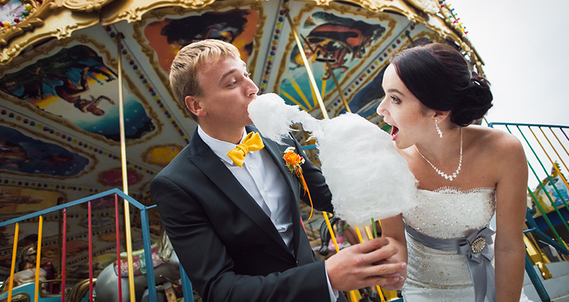A photo of a newlywed couple eating cotton candy in an amuesement park. A carousel behind them.
