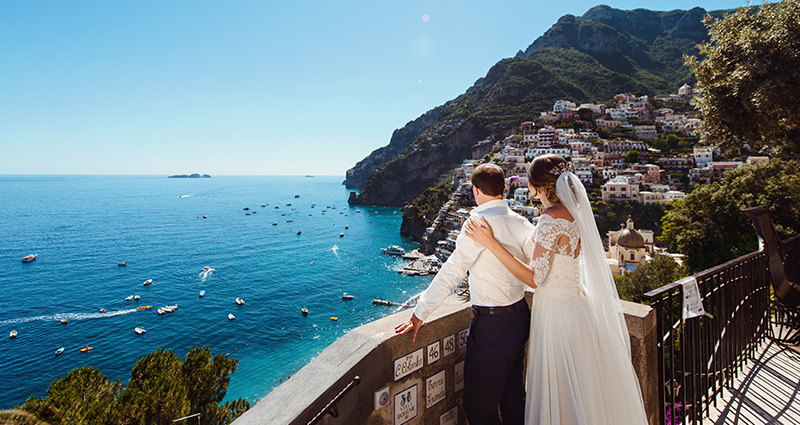 A photo of newlyweds looking at the sea on a terrace in Amalfi.