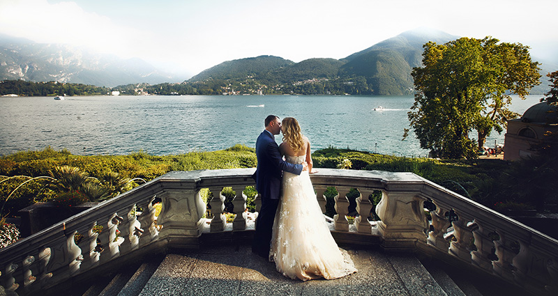 A photo of newlyweds standing on top of stairs. Lake Como and mountains in the background.