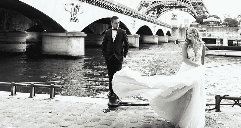 A black and white photo of a newlywed couple near Seine. A bridge and the Eiffel tower in the background.