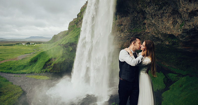 A romantic photo of newlyweds with a waterfall in the background, Iceland.