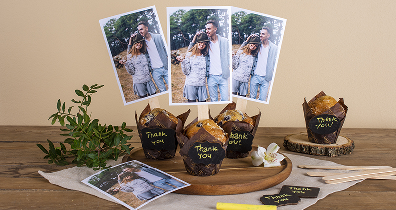 Rectangular photos glued to ice cream sticks and sticked into muffins with 'Thank you' caption on them. Muffins on a wooden tray placed on a light cloth and dark table, a print, green brunch, yellow  chalk and thank you cards around it.