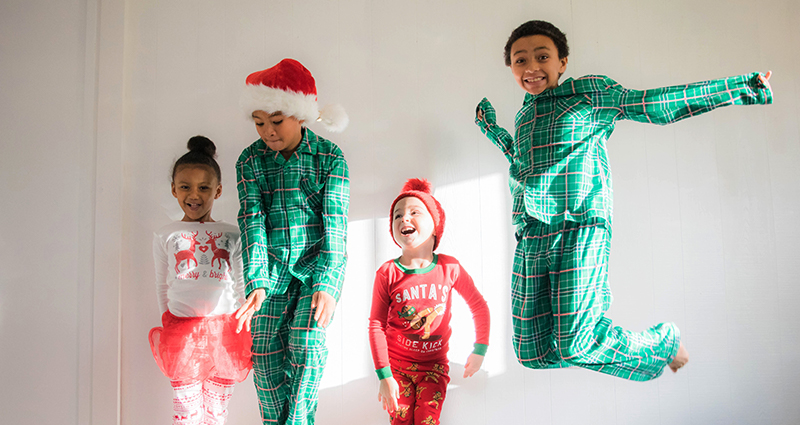 Four jumping kids wearing Christmas pyjamas, a white wall in the background