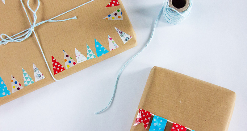Gifts packed in grey paper, decorated with colourful christmas trees.