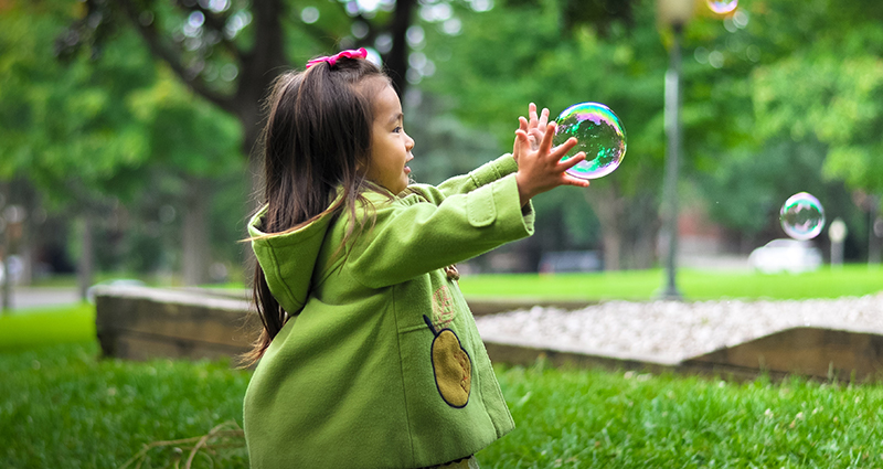 Girl in the park catching soap bubbles