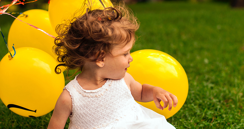 Girl wearing a white dress with yellow balloons in the parkUne fillette avec une robe avec des ballons jaunes dans un parc.