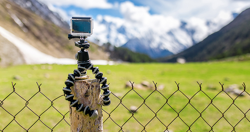 GoPro camera on a portable tripod GorillaPod located on a wooden stake; meadow, mountains and sky in the background