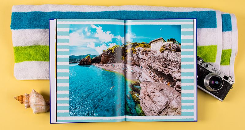 Holiday photobook with a picture of a rocky seashore, a blue and green striped towel in the background, next to a camera and a shell