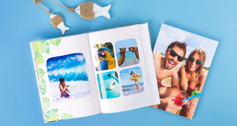 Holiday photobooks – one of them with a photo collage is open, the closed one's cover presents a photo of a couple, two wooden fish above them.