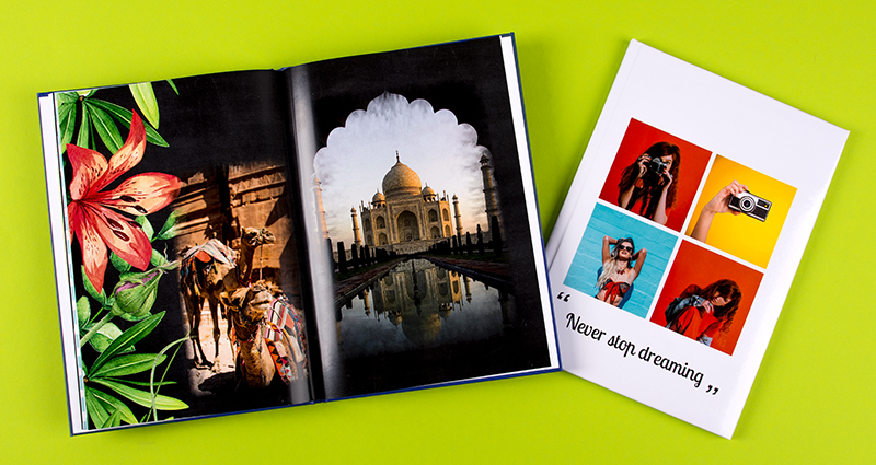 "Holiday photobooks, an open one with a clipart showing a huge flower and leaves on the left side of the page, a closed one with a collage of photos on the cover with a text ""Never stop dreaming"""