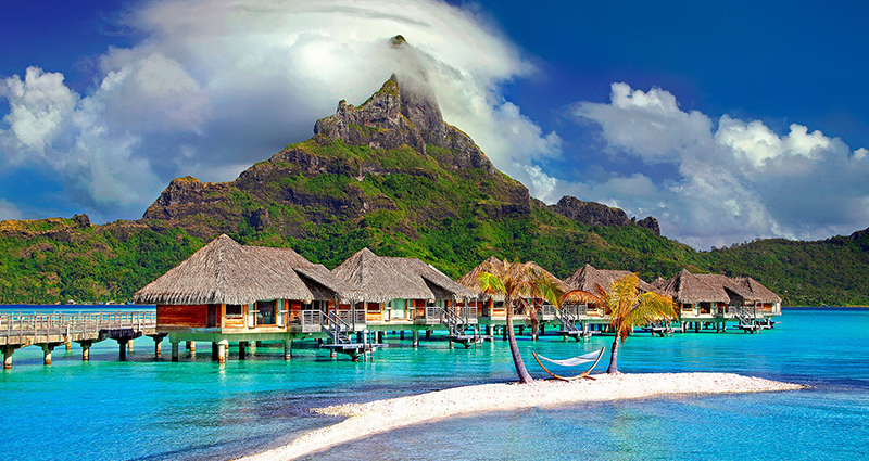 Houses by azure ocean, mountains in the background