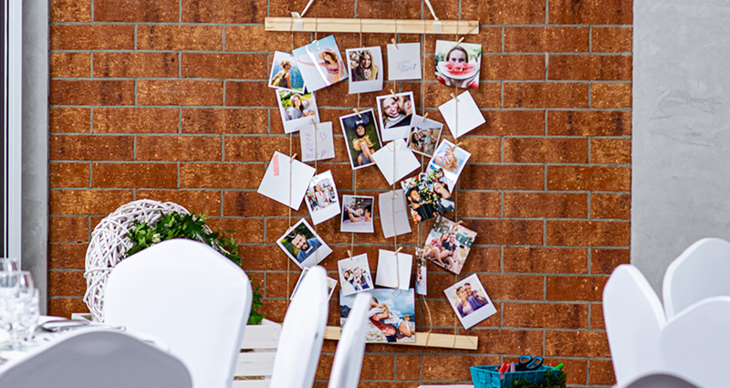 Insta Photos presenting the wedding guests, photos are attached to hemp strings tied to wooden slats placed on a brick wall. Wedding tables decorated with white cloth in the foreground