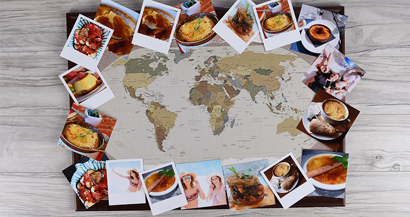 Insta photos and retro prints of food lying around the world map