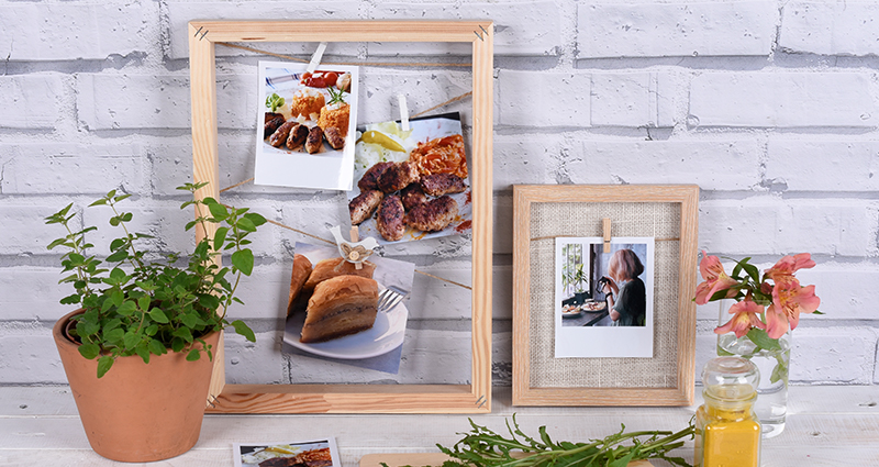 Insta photos and retro prints of food, some of them in a frame, others lying on the table next to potted herbs and a chopping board with cherry tomatoes