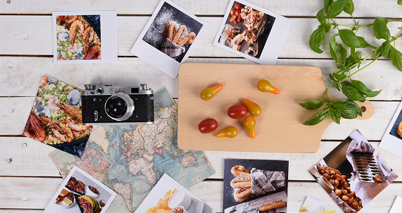 Insta photos and retro prints of food, the world map in the background lying next to a camera, a chopping board and a basil sprig