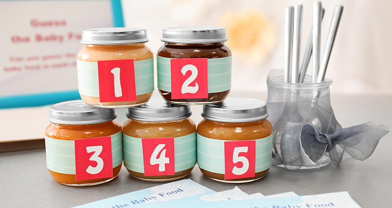 Jars with baby food with covered labels, spoons and pieces of paper to write down the answers.