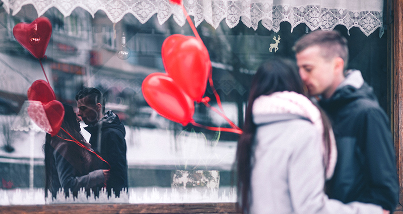 Kissing couple holding red heart-shaped balloons