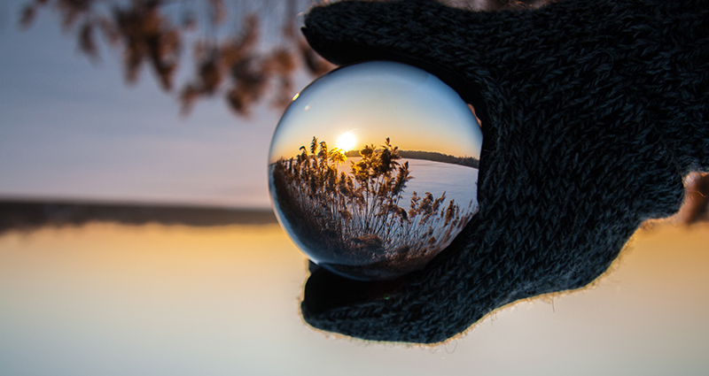 Lake and swards reflected in a ball which is hold by a gloved hand