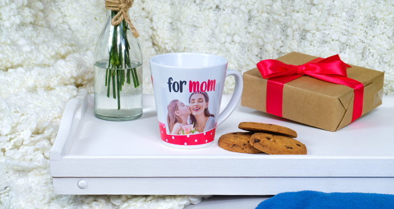 "Latte Mug with a photo of a mom and daughter and a ""for mom"" caption. The mug is on a white tray near a vase with flowers, a gift with a ribbon and cookies."