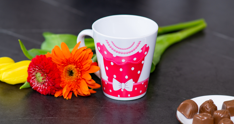 Latte Mug with a pink polka dot dress theme. Next to that spring flowers and chocolates on a plate.