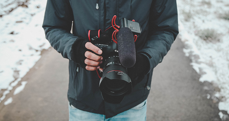 Man holding a camera in hands in fingerless gloves; focus on his body
