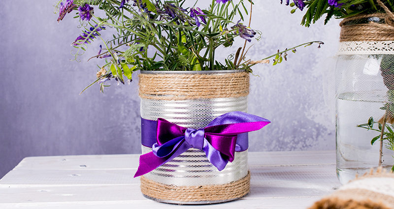 Meadow flowers in a can decorated with a netting, a jute string and ribbons next to the flower jar